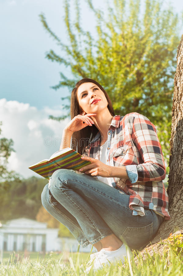 Low angle shot of attractive woman with open book. In the park resting and enjoying spring royalty free stock image