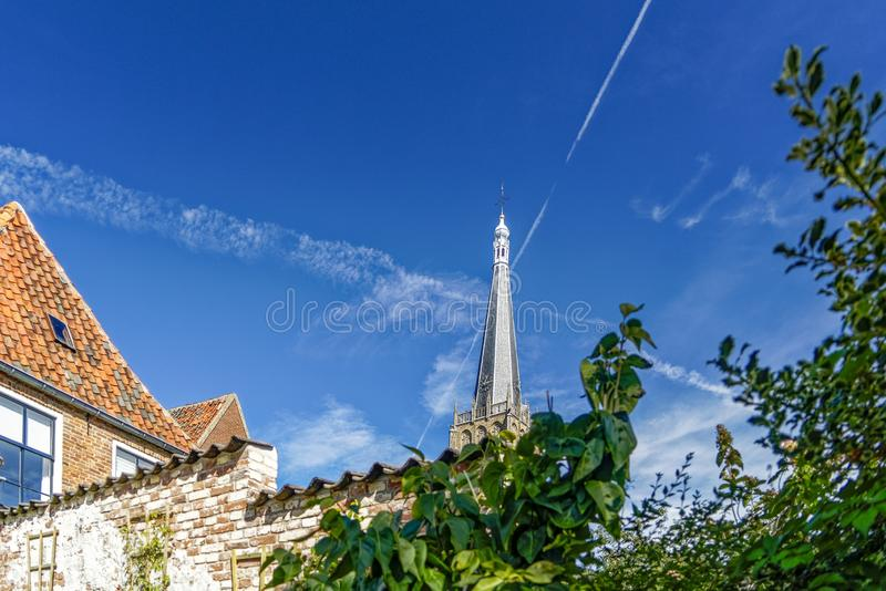 Low angle shot of a church spire with a cross on the top in Doesburg, Netherlands. A low angle shot of a church spire with a cross on the top in Doesburg stock image