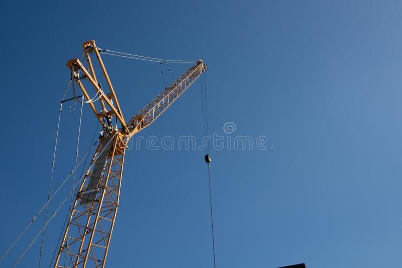 Low angle shot of a crane under a blue sky with several metal cords attached to it. A low angle shot of a crane under a blue sky with several metal cords stock photos
