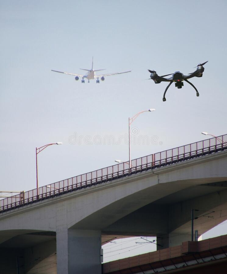 Low angle shot of a drone and an airplane flying next to each other over a bridge stock photos
