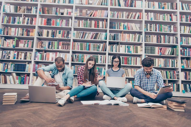 Low angle shot of four international clever bookworms students i. N the library studying, sitting with crossed legs on the floor together, using books and royalty free stock photography