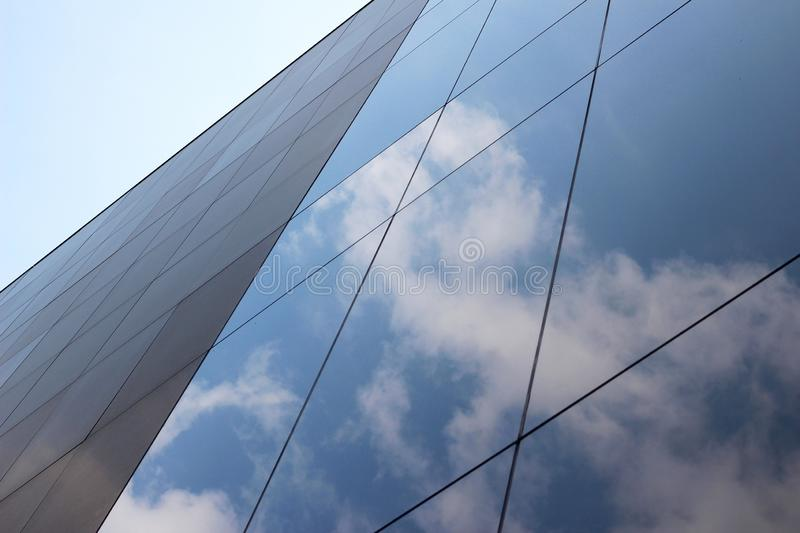 Low angle shot of a glass high-rise business building with a reflection of clouds and the sky on it. A low angle shot of a glass high-rise business building with stock photos