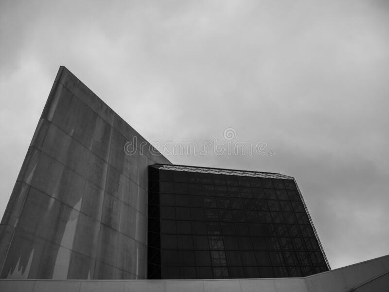 Low angle shot of a modern building with glass panels against a cloudy sky in grayscale. A low angle shot of a modern building with glass panels against a cloudy royalty free stock image