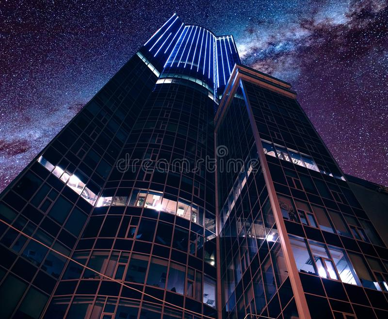 Low angle shot of a modern futuristic business architecture under a breathtaking starry sky. A low angle shot of a modern futuristic business architecture under royalty free stock photo