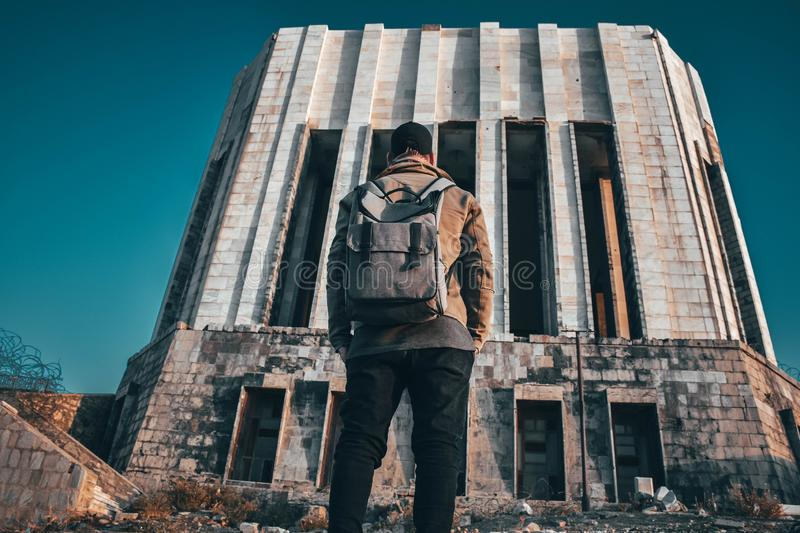 Low angle shot of a person in a backpack standing in front of a large abandoned building stock photos