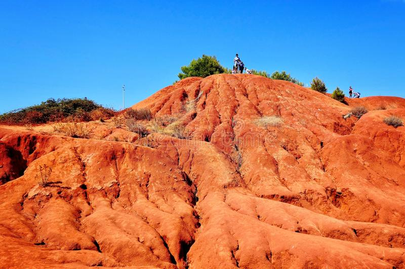 Low angle shot of a person standing on top of the deserted mountain with a clear sky in background. A low angle shot of a person standing on top of the deserted royalty free stock photography