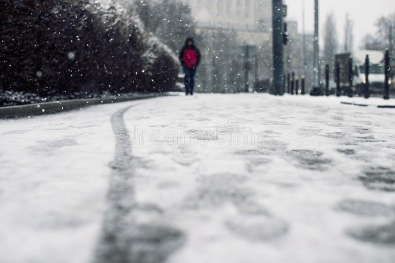 Low angle shot of a person walking on the snow covered sidewalk under the snow. A low angle shot of a person walking on the snow covered sidewalk under the snow royalty free stock photo