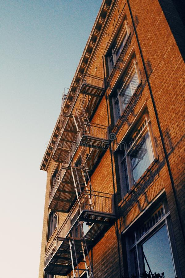 Low angle shot of a red brick apartment building with fire escape staircase in San Francisco. A low angle shot of a red brick apartment building with fire escape royalty free stock photo