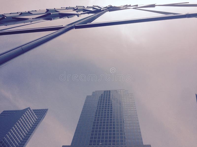 Low angle shot of the reflection of a skyscraper in the mirror walls of a building royalty free stock photos