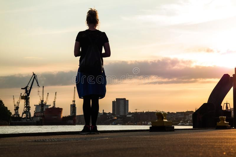 Low angle shot silhouette of woman in blue dress standing on pier. With harbor structures in background royalty free stock photography