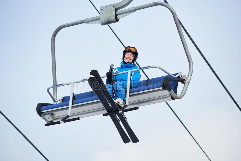 Low angle shot of a smiling female skier in blue ski suit riding up to the top of the mountain on a cable ski lift. With skies at winter ski resort. Ski season stock photos