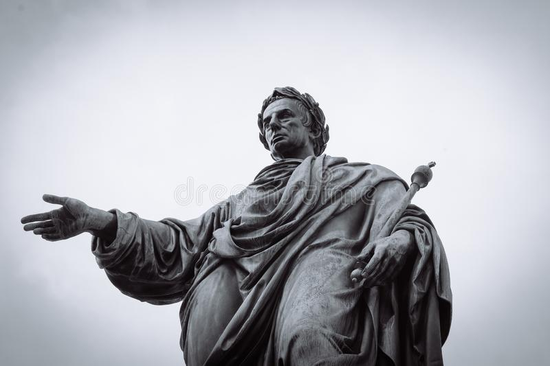 Low angle shot of a statue of a male with robe holding a staff in black and white royalty free stock images