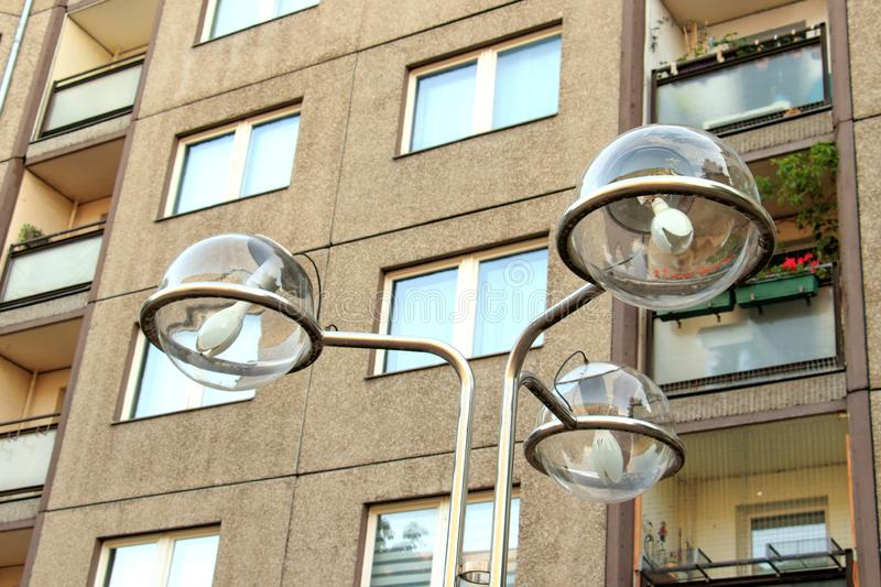 Low angle shot of street lights in front of a brown building with plants on the windows. A low angle shot of street lights in front of a brown building with royalty free stock photo