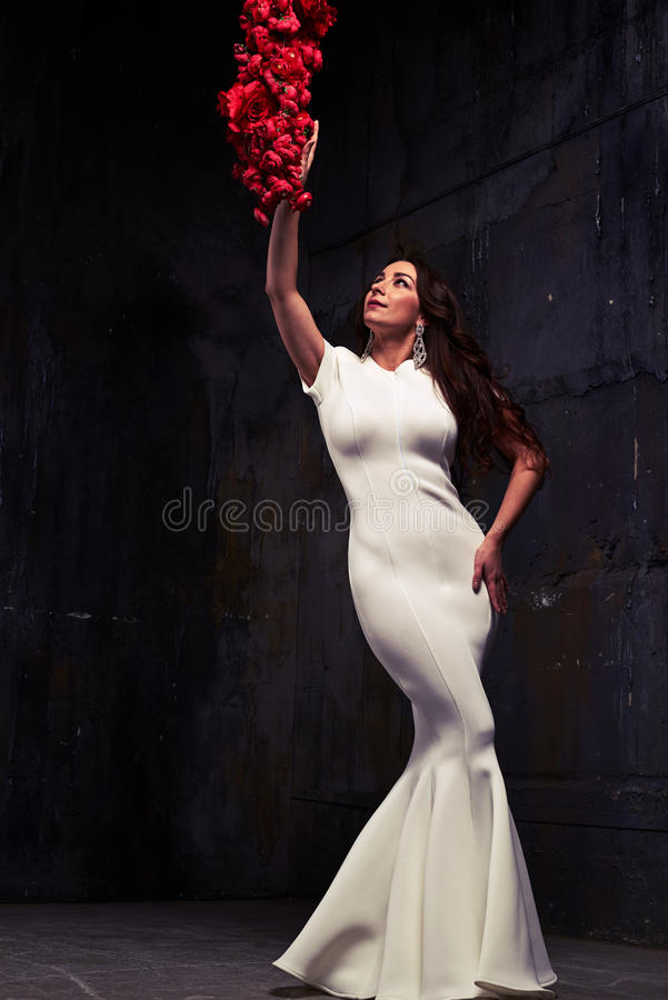 Low angle shot of stunning woman in white evening dress touching stock images