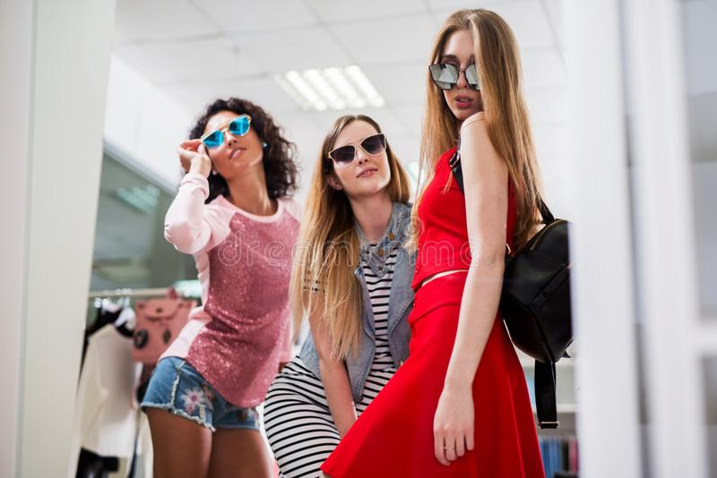 Low-angle shot of stylish glamorous girlfriends choosing new clothes and sunglasses standing posing in front of the. Mirror in showroom stock photos
