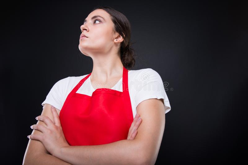 Low angle shot of supermarket female employee. Standing with folded arms and looking up stock photography