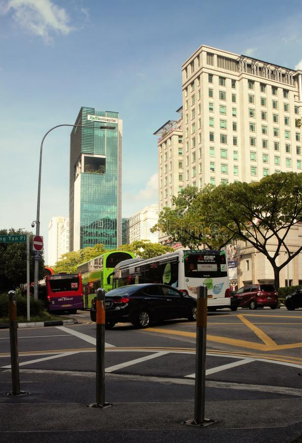 Low angle shot of traffic in downtown Singapore with the Raffles Hospital seen in the background stock photo