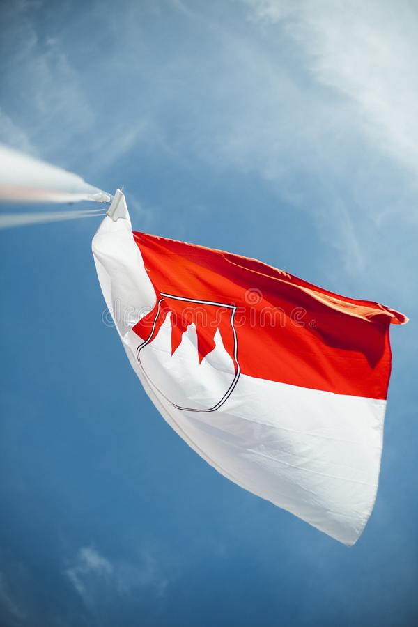 Low angle shot of a white and red flag under the beautiful blue cloudy sky on a bright sunny day royalty free stock images
