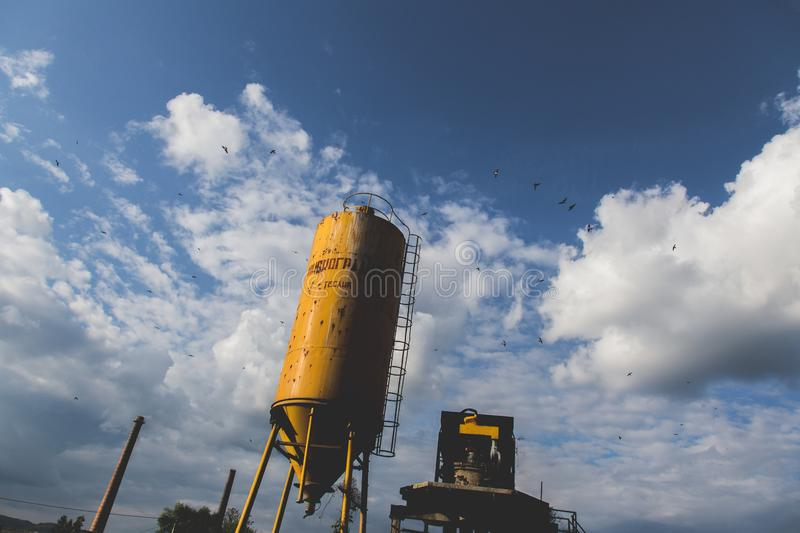 Low angle shot of a yellow metal tank with a cloudy sky in the background royalty free stock photo