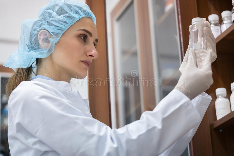 Woman chemist finding the perfect substance during experimental. Low-angle side view of a female chemist happy for finding the perfect chemical substance during royalty free stock images