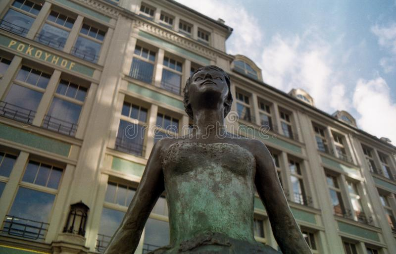 Low angle on the statue. Frog perspective on the statue on the background of the building and sky facade stock photography