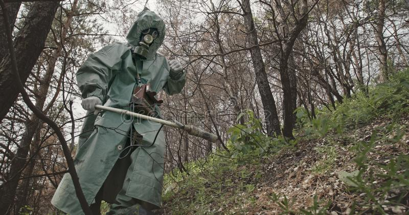 Low angle unrecognizable guy in hazmat suit and gas mask searching for radiation with Geiger counter in abandoned forest. Near Chernobyl stock image