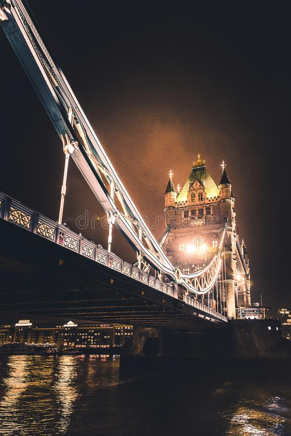Low angle vertical shot of the beautifully lighted London Tower Bridge at night. A low angle vertical shot of the beautifully lighted London Tower Bridge at stock photography