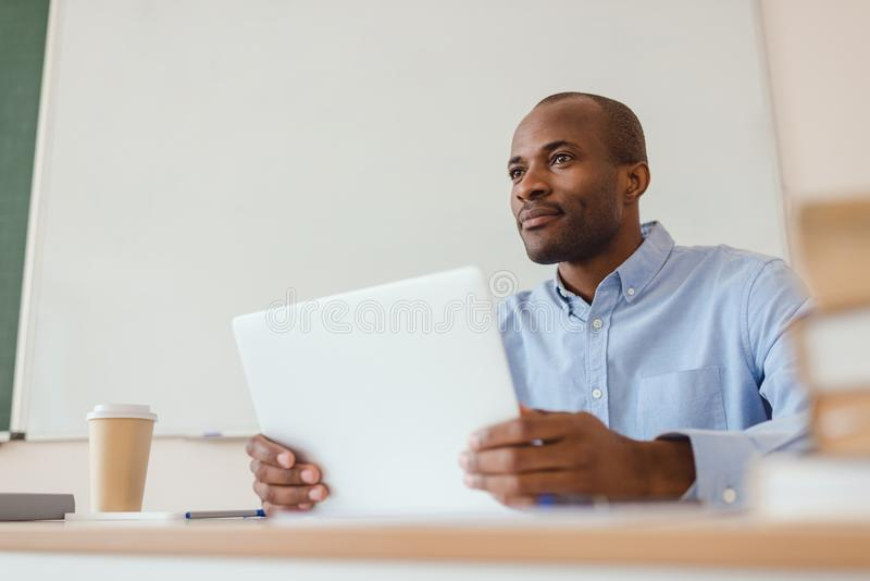 Low angle view of african american teacher sitting at desk with laptop and coffee royalty free stock photography