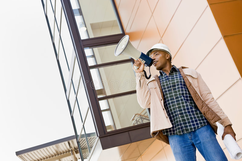 Low angle view of African construction worker. Making announcement into bullhorn stock photos