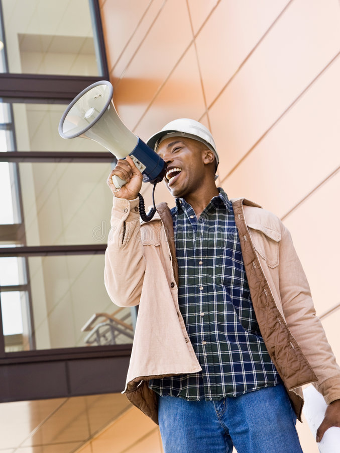 Low angle view of African construction worker. Making announcement into bullhorn stock image