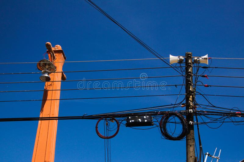 Low angle view against blue sky on isolated high voltage power poles with electric wires, distribution transformer and stock photography