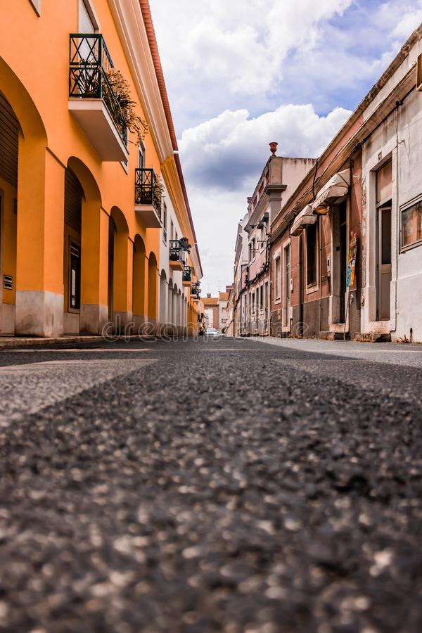 Low angle view of an alleyway in setubal Portugal with  classic buildings on both side and clouds in sky. Alley, angle, architecture, area, asphalt, avenue royalty free stock photography