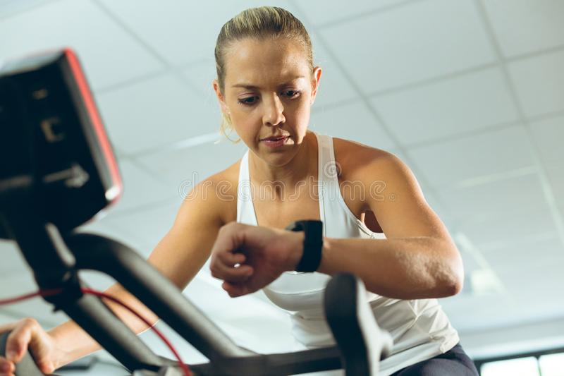 Woman checking time while exercising with exercise bike in fitness studio stock images