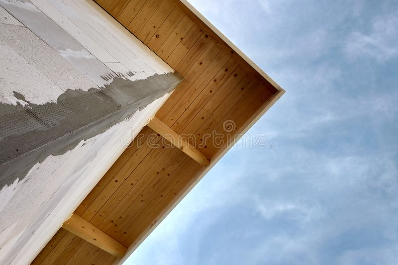 Low angle view of a building fasade under construction unfinished wall and wooden roof boards.  stock photo