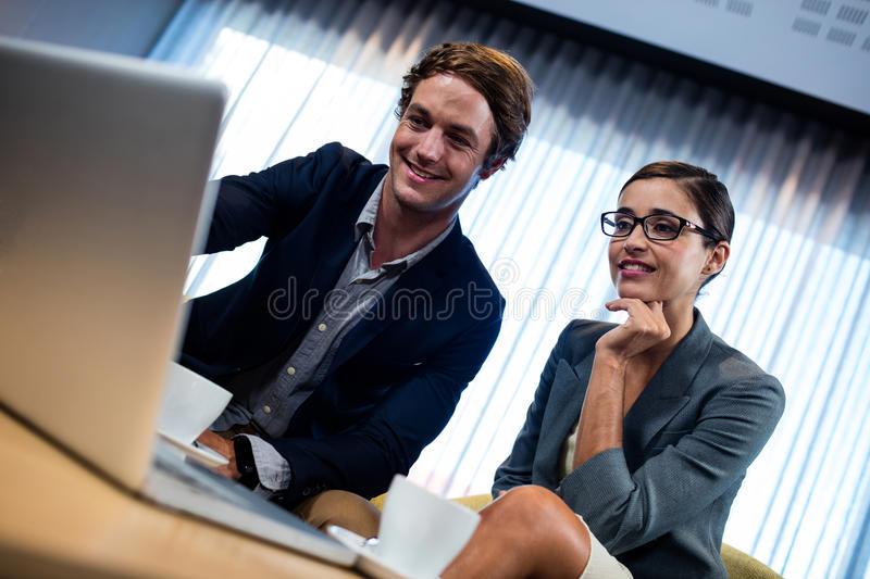 Low angle view of business associate looking a laptop. At the office royalty free stock photography