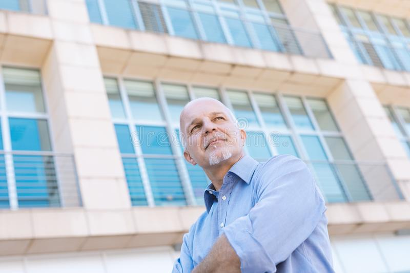 Low angle view of senior man looking off. Low angle view of Business man looking off in the distance with backdrop of windows stock photography
