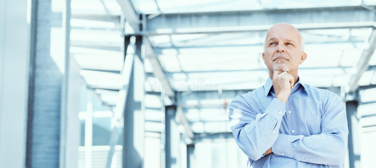 Low angle view of Business man. In corridor looking off in the distance with arms folded and hand on chin blue tones stock photo