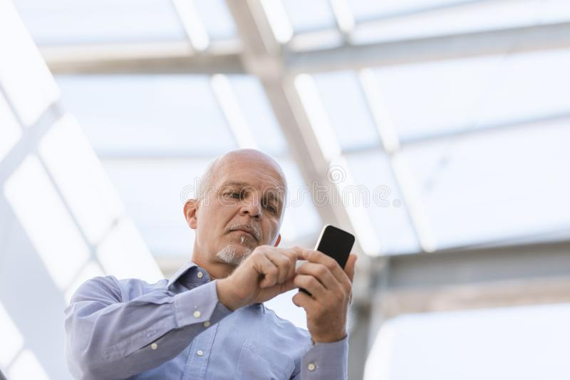 Low angle view of man texting on his mobile stock image