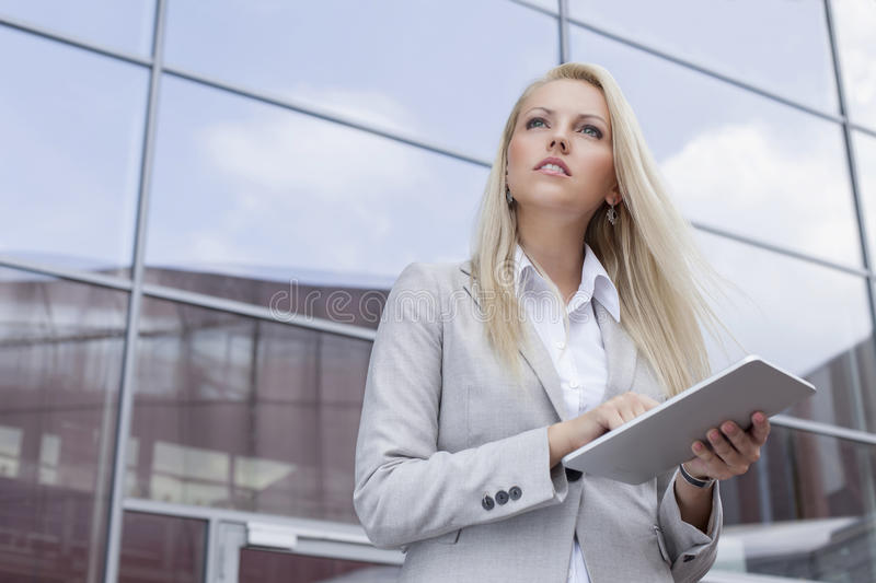 Low angle view of businesswoman holding digital tablet while looking away against office building stock photography