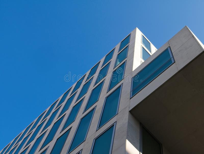 Low angle view of cantilevered contemporary building against blue sky. Diminishing perspective view royalty free stock photo