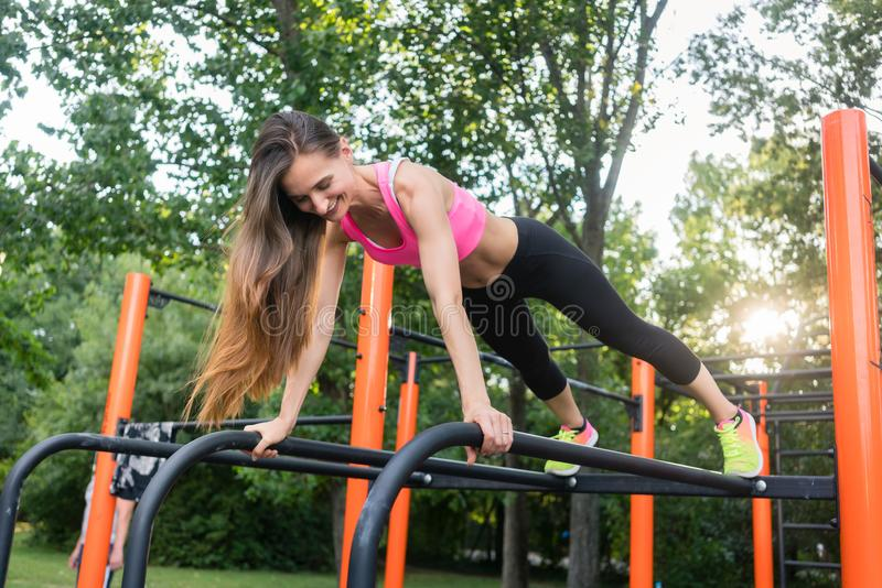 Cheerful beautiful woman exercising basic plank position outdoor. Low-angle view of a cheerful beautiful woman passionate about calisthenics training exercising stock image