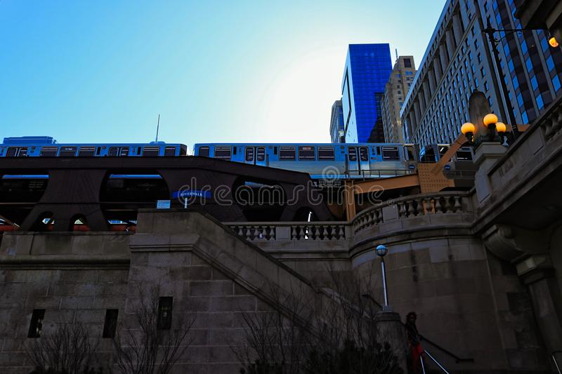 Low angle view of Chicago elevated `el` train over Wells Street with stairs leading down to riverwalk. Chicago, IL / USA - 4/30/18: Low angle view of Chicago stock photography