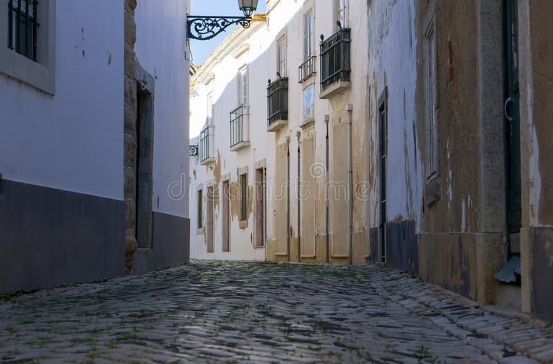 Low angle view of cobbled street in Faro, Algarve, Portugal. With traditional white painted rustic houses royalty free stock image