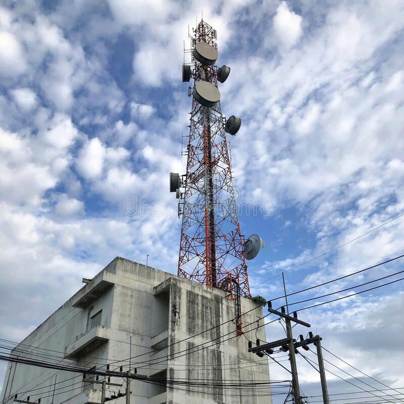 Low angle view of communication tower on building against sky stock images