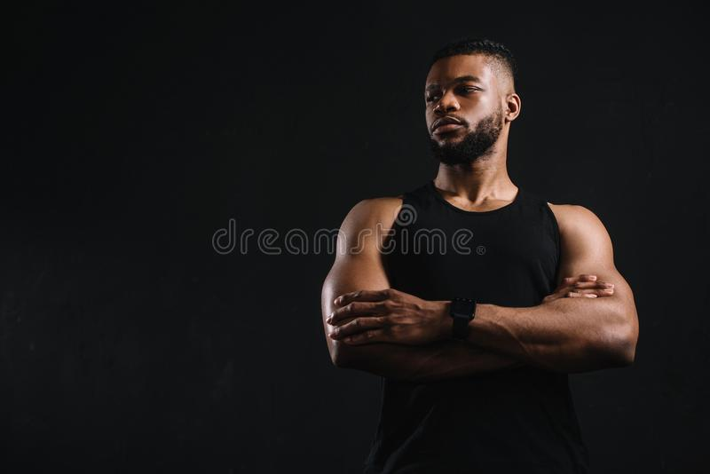 low angle view of confident african american sportsman standing with crossed arms and looking away stock images