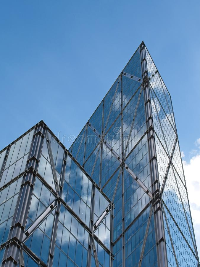Low angle view of Contemporary Metallic Skyscrapers against blue sky,. Low angle view of contemporary skyscrapers against blue sky. Reflection of blue sky and stock image