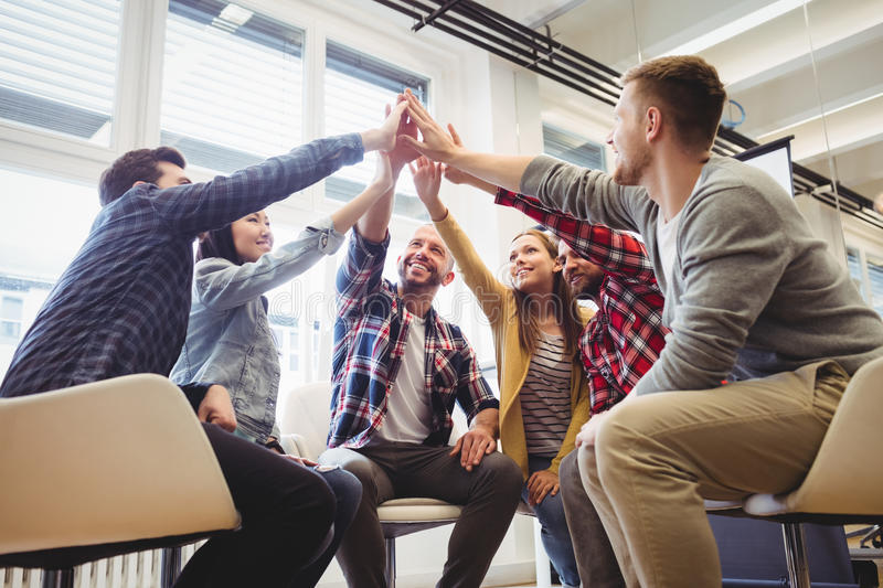 Low angle view of creative business people giving high-five stock photos