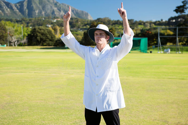 Low angle view of cricket umpire signalling six at match stock photography