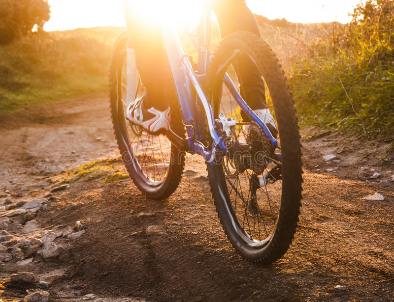 Low angle view of cyclist riding mountain bike trail at sunrise stock photography