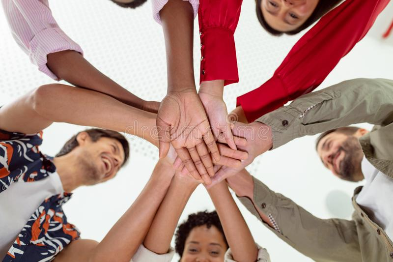 Business people forming hand stack in a modern office. Low angle view of diverse business people forming hand stack in a modern office stock photo